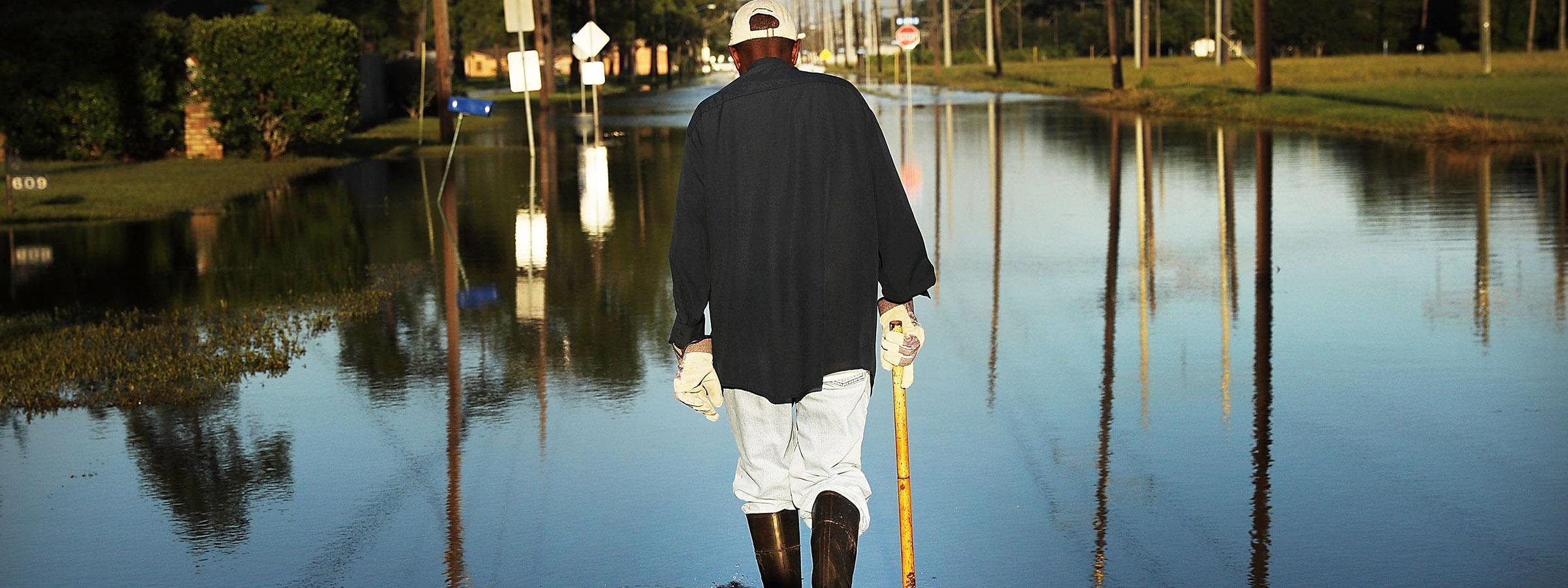 Man walking on flooded streets after a hurricane.