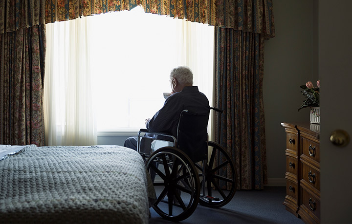 image of an elderly male in a wheelchair facing a window and holding a cup of tea