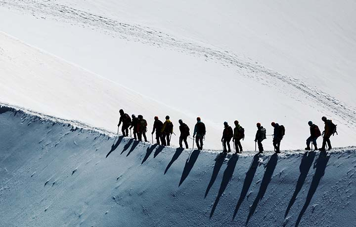 Photograph of mountain climbers ascending a ridge together