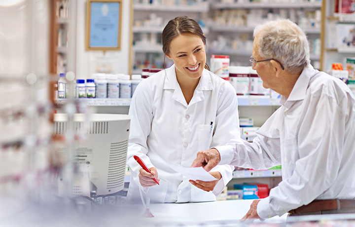 image of a female pharmacist conferring with an older male patient