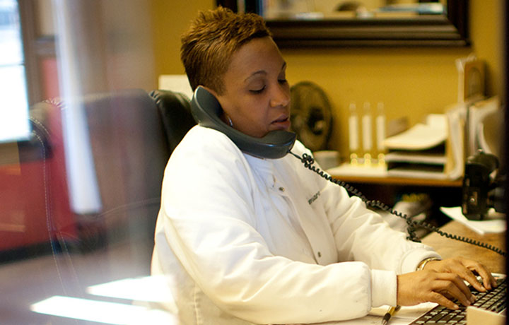 image of a female front office healthcare staffer answering a telephone and typing on a computer