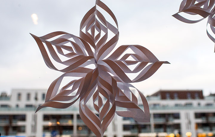 image of a paper snowflake hanging in a window
