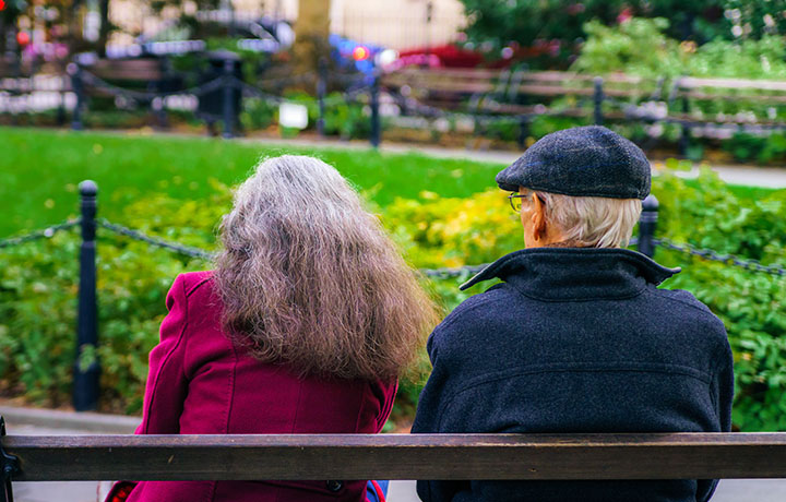 baby boomer couple sitting on a bench as seen from behind
