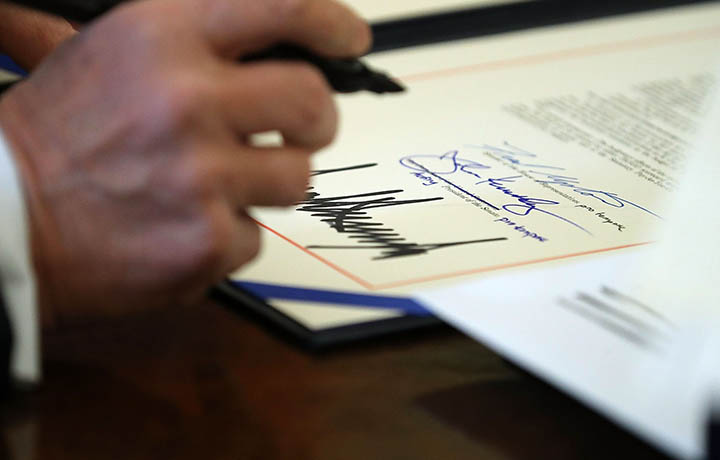 Image of President Trump signing the tax reform bill into law