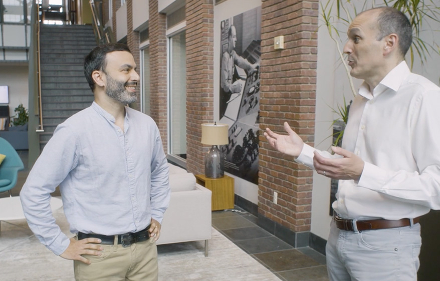 Simon Mouyal and Brett Connor chat in the main lobby of athenahealth's Watertown location.